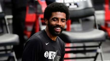Kyrie Irving #11 of the Nets shares a
