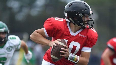 Matthew Ranges #10, Syosset quarterback, looks upfield before
