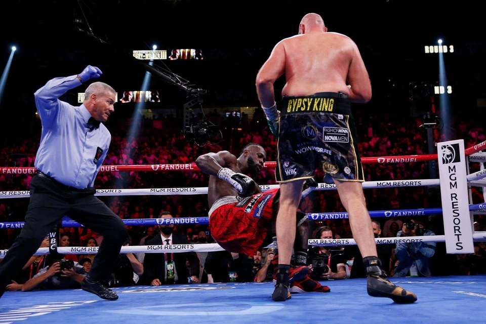 Tyson Fury, of England, knocks down Deontay Wilder