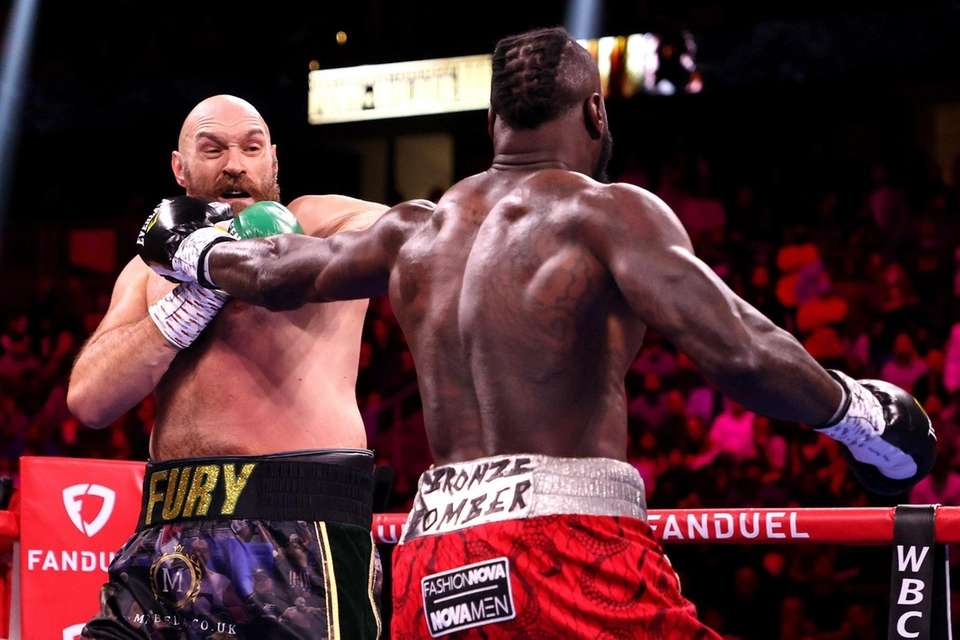 Deontay Wilder (R) punches Tyson Fury during their