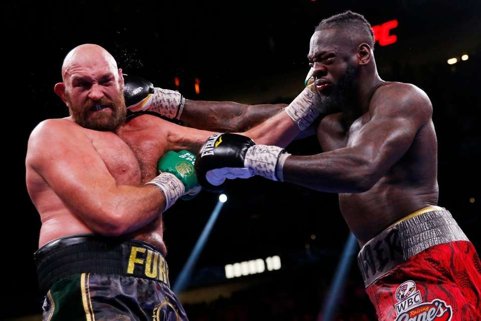 Deontay Wilder, right, and Tyson Fury, of England,