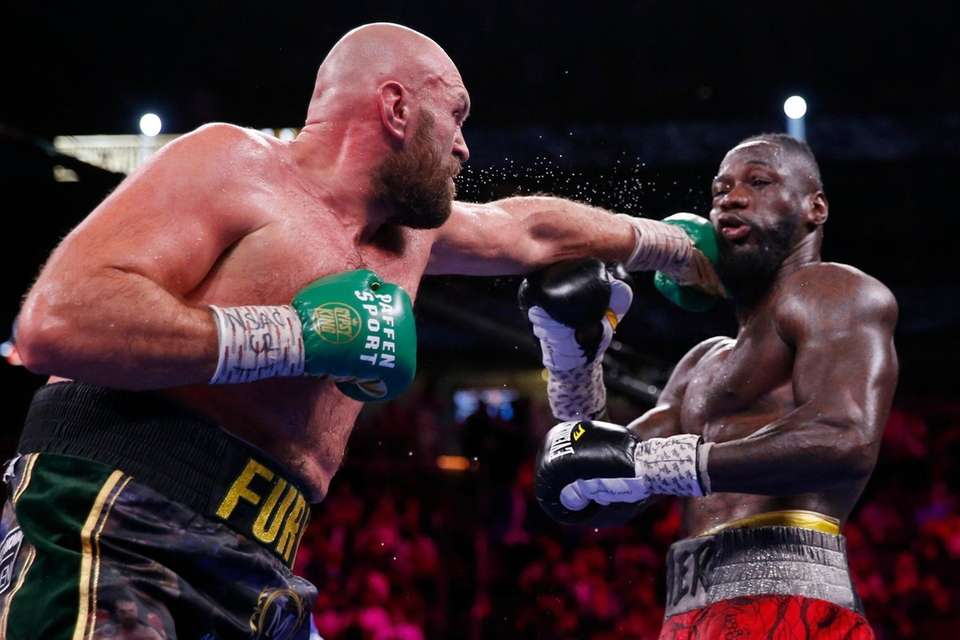 Tyson Fury, of England, hits Deontay Wilder in