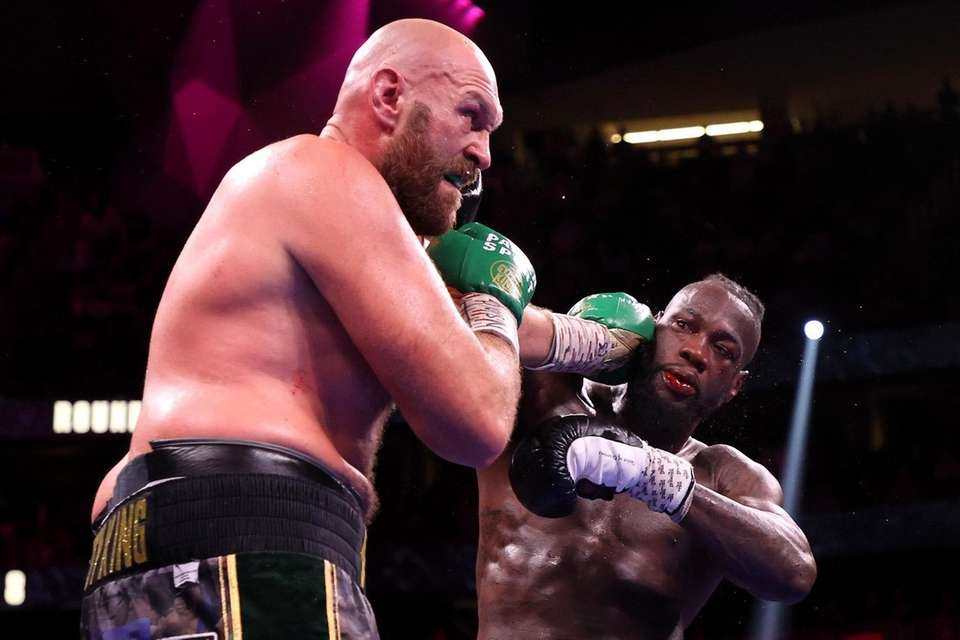 Tyson Fury (L) punches Deontay Wilder during their