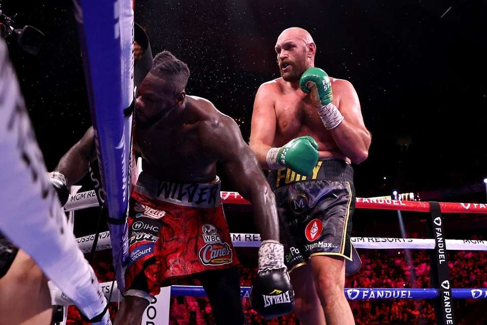 Deontay Wilder (L) is knocked out by Tyson