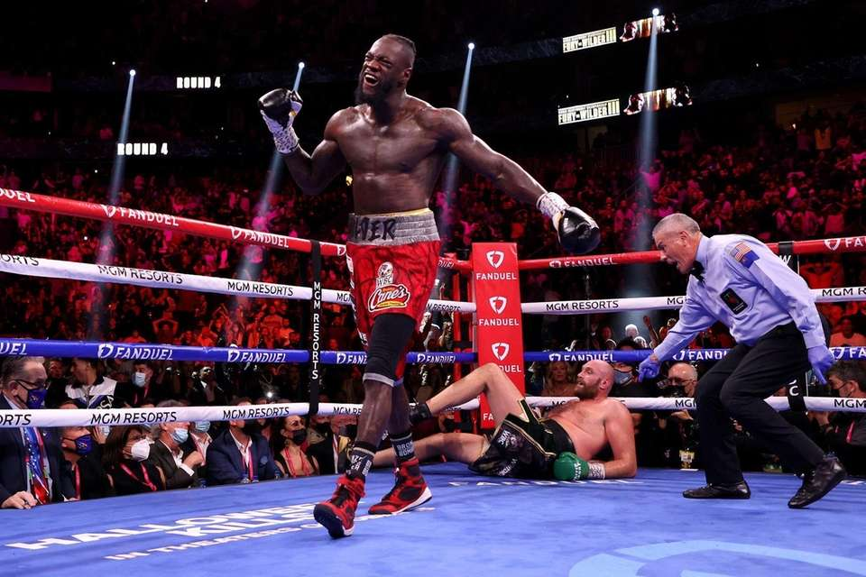 Deontay Wilder (L) reacts after knocking down Tyson