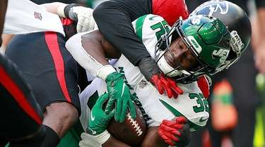 Jets running back Michael Carter is tackled during