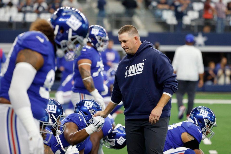 Giants head coach Joe Judge, right, greets his