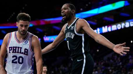 The Nets' Kevin Durant, right, reacts past the