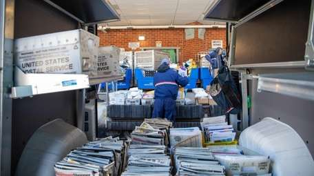 Letter carrier Jong Kwon loads his mail truck