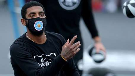 Brooklyn Nets guard Kyrie Irving tosses autographed mini