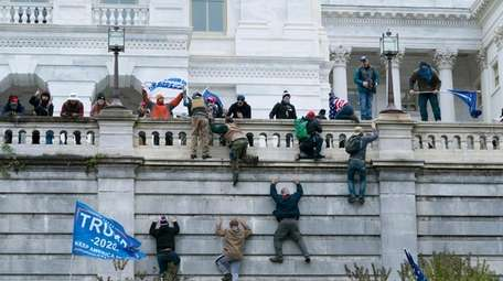 Violent insurrectionists loyal to President Donald Trump scale