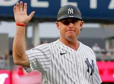 Yankees third base coach Phil Nevin waves to