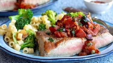 Seared tuna topped with tomatoes, olives, garlic, and