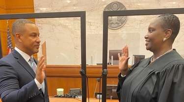 Breon Peace, left, is sworn in Friday as