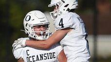 Charlie McKee #7, Oceanside quarterback, left, gets congratulated