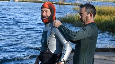 Tom Collings, left, of Bellmore, prepares to enter