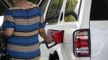 A customer pumps a gas at a station