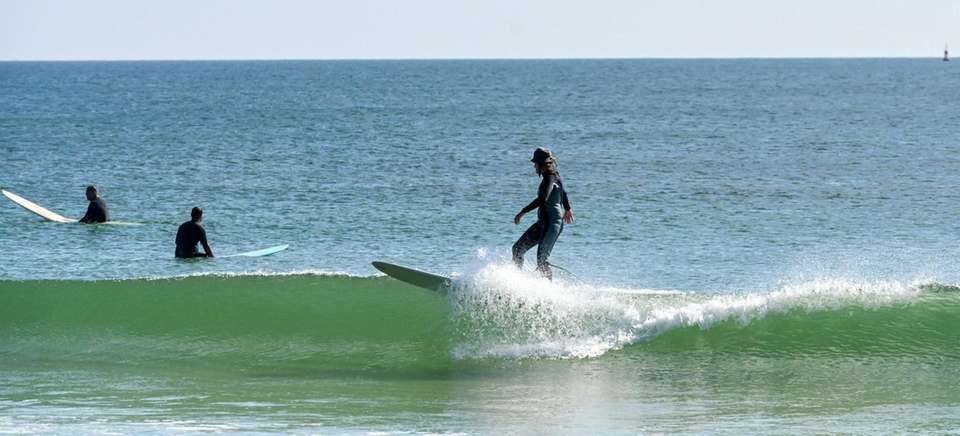 A surfer rides the waves at Ponquogue Beach