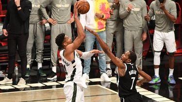 Milwaukee Bucks forward Giannis Antetokounmpo shoots over Nets