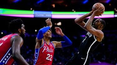 Nets' Kevin Durant, right, goes up for a