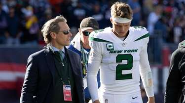 Jets quarterback Zach Wilson is escorted from the