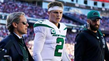 Jets quarterback Zach Wilson is escorted to the