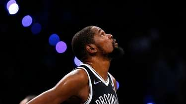 Nets forward Kevin Durant looks at the score