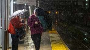 Commuters contend with heavy rain at the Long