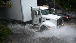 A tractor trailer navigates through water on Route