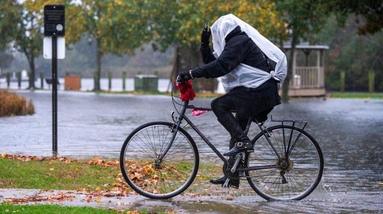 A woman rides her bike through heavy rainfall