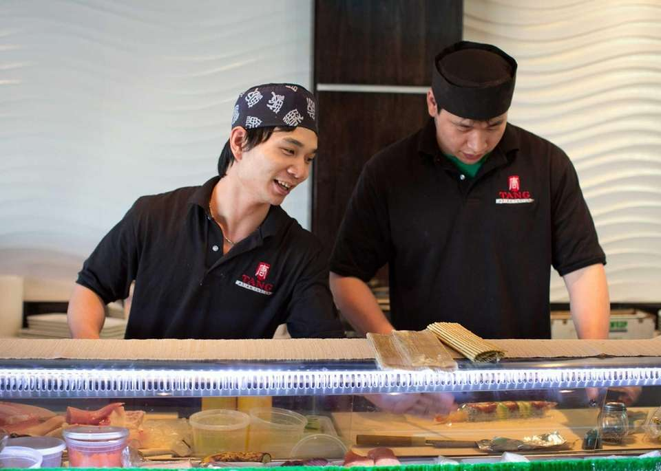 Chefs work behind the sushi bar at Tang