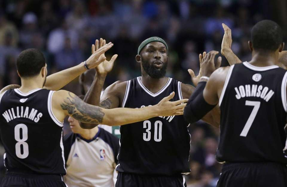 Nets forward Reggie Evans celebrates with guards Deron