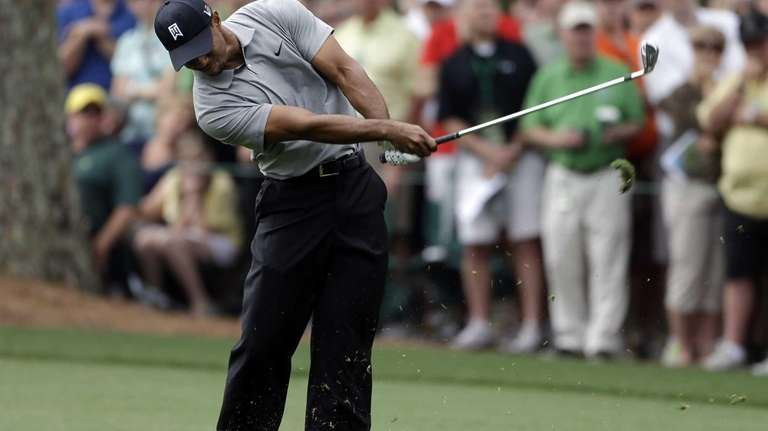 Tiger Woods hits on the first fairway during