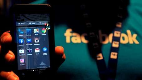 Facebook employee displays an HTC phone with the