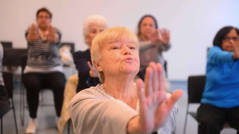 Magda Rosenberg leads a chair yoga class at