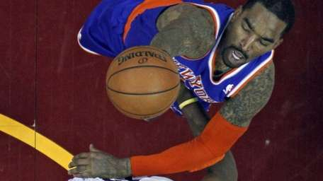 Knicks' J.R. Smith, top, shoots over Cleveland Cavaliers'