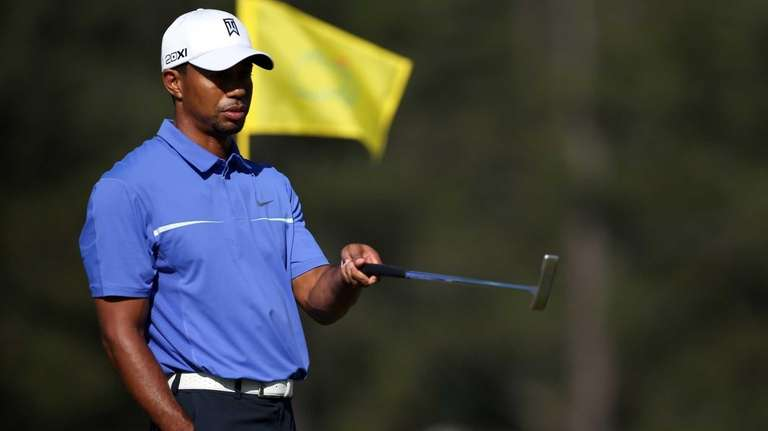 Tiger Woods walks across a green during a