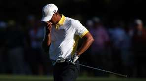 Tiger Woods reacts after hitting the flag and