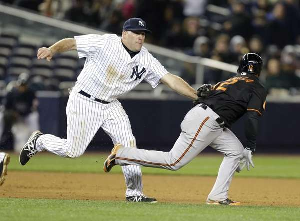 Yankees third baseman Kevin Youkilis, left, tags out