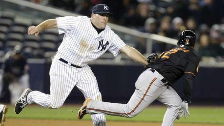 Yankees third baseman Kevin Youkilis, left, tags out