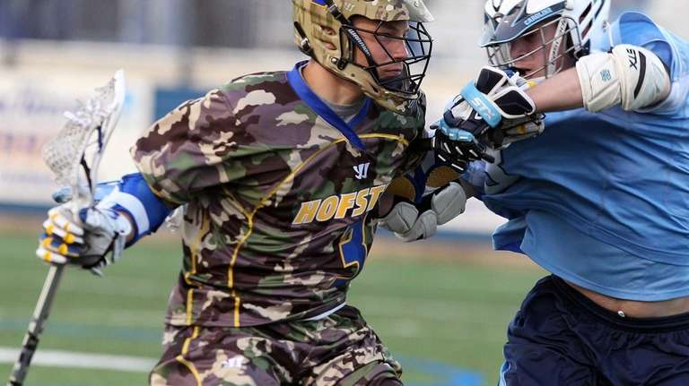 Hofstra's Tyler Johnston takes a hit from UNC's