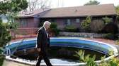 A homicide detective walks by a backyard pool