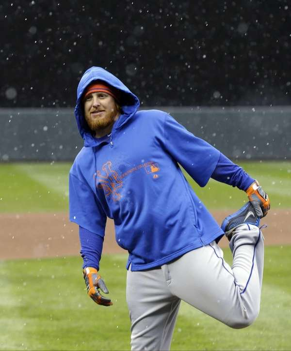 Justin Turner stretches as snow falls before batting