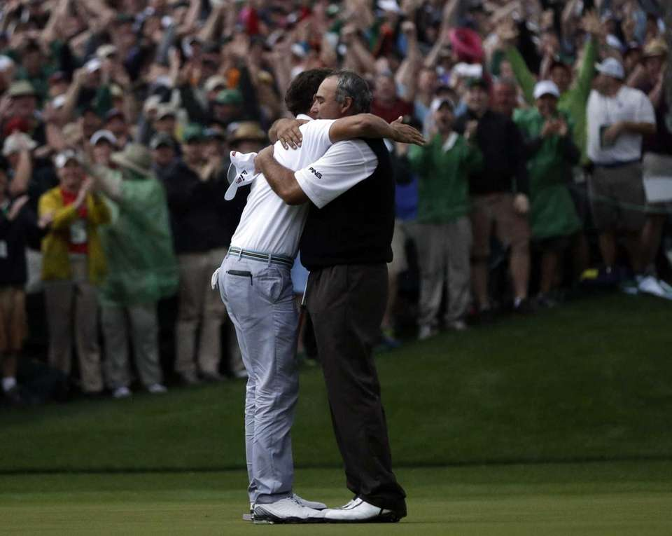Adam Scott hugs Angel Cabrera after making a