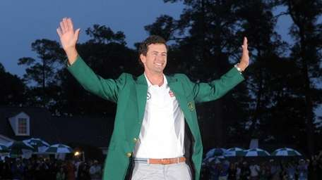 Adam Scott smiles after being presented with the