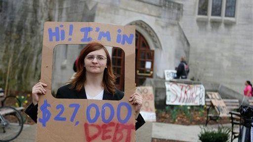 Indiana University senior Randall Burns holds a sign