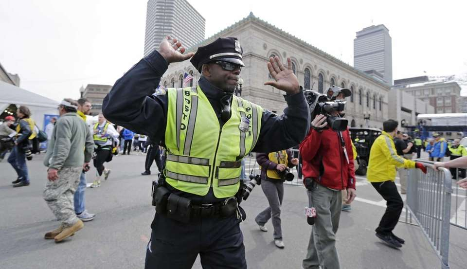 A Boston police officer clears Boylston Street following