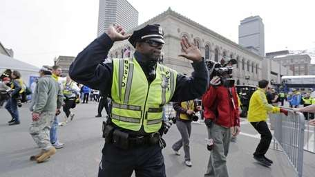A Boston police officer clears Boylston Street following