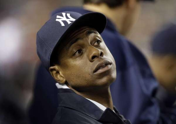 Curtis Granderson sits in the dugout watching a