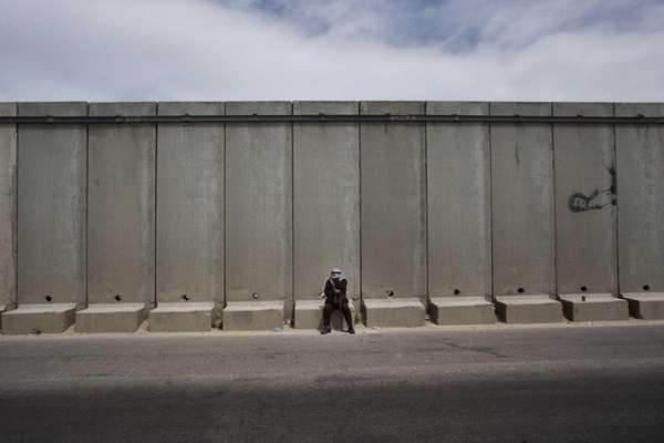 A Palestinian man pauses near the Qalandia checkpoint